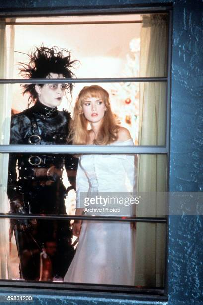 Johnny Depp and Winona Ryder looking out window in a scene from the film 'Edward Scissorhands' 1990