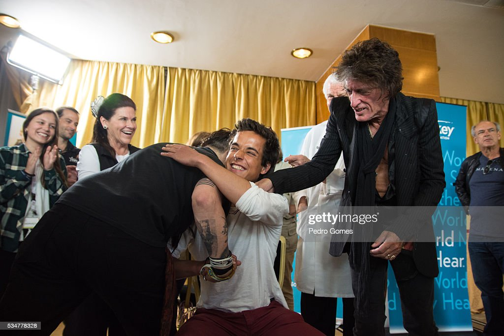 <a gi-track='captionPersonalityLinkClicked' href=/galleries/search?phrase=Johnny+Depp&family=editorial&specificpeople=202150 ng-click='$event.stopPropagation()'>Johnny Depp</a> hugs a patient of the Starkey Hearing Foundation next to <a gi-track='captionPersonalityLinkClicked' href=/galleries/search?phrase=Joe+Perry+-+Muzikant&family=editorial&specificpeople=13600677 ng-click='$event.stopPropagation()'>Joe Perry</a> at Four Season Hotel Ritz Lisbon on May 27, 2016 in Lisbon, Portugal.