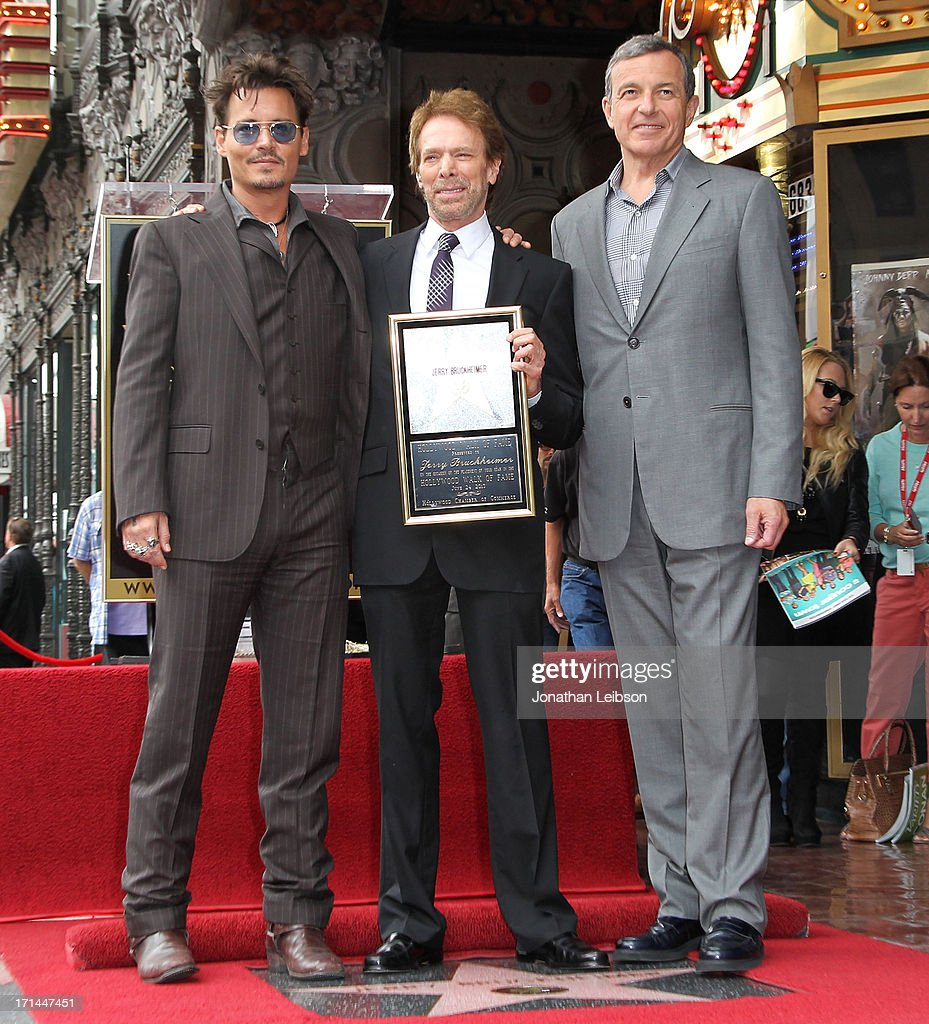 Johnny Depp, Jerry Bruckheimer and Bob Iger pose as Bruckheimer is honored on the Hollywood Walk Of Fame on June 24, 2013 in Hollywood, California.