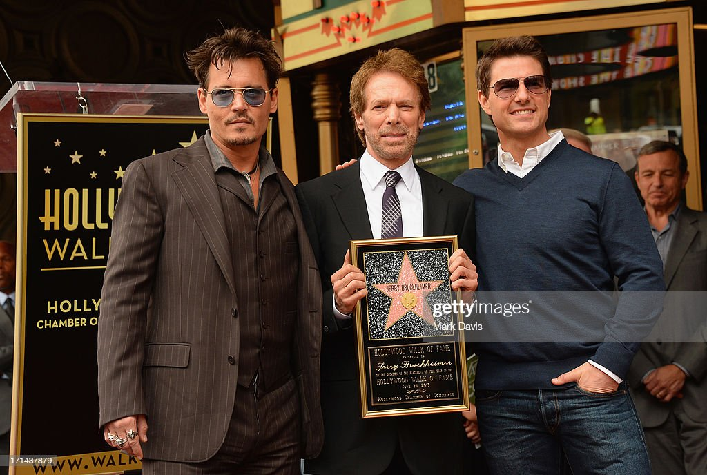 Johnny Depp, Jerry Bruckheimer and Tom Cruise pose as Jerry Bruckheimer is honored on the Hollywood Walk Of Fame on June 24, 2013 in Hollywood, California.