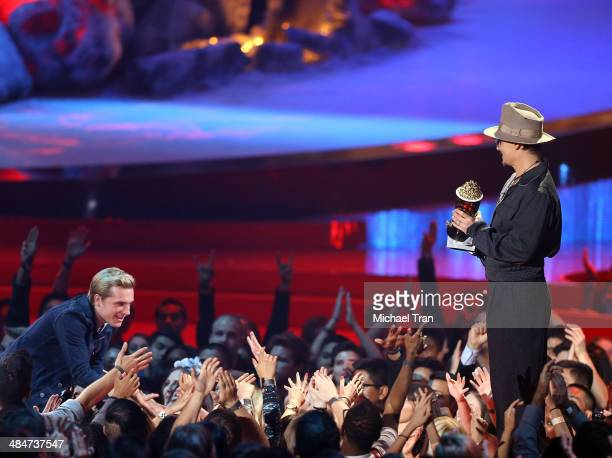 Johnny Depp presents actors Josh Hutcherson with the Movie of the Year award for 'The Hunger Games Catching Fire' onstage during the 2014 MTV Movie...