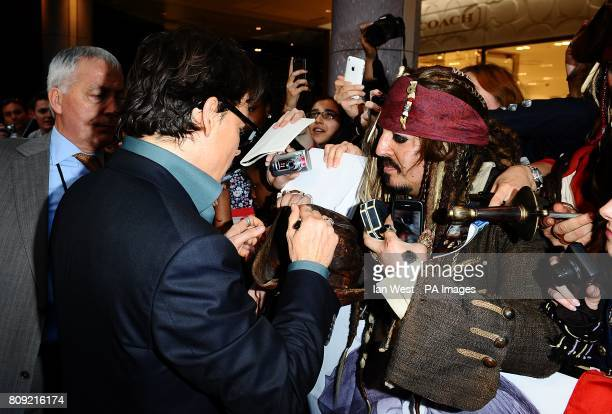 Johnny Depp signs autographs for fans as he arrives for the UK film premiere of Pirates of the Caribbean On Stranger Tides at the Vue Westfield London