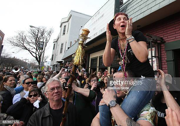Johnny D's owner Carla DeLellis sits on the shoulders of a former bartender Oscar Simoza of Somerville seeing for the first time the size of the...