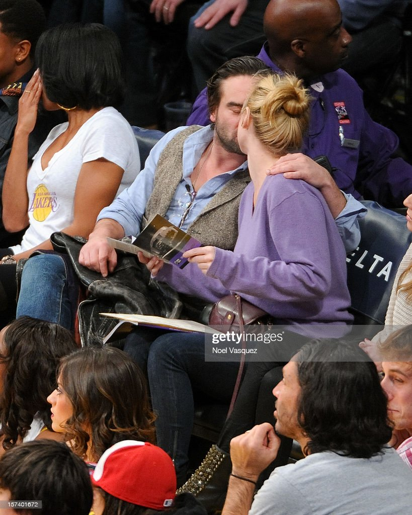 <a gi-track='captionPersonalityLinkClicked' href=/galleries/search?phrase=Johnny+Galecki&family=editorial&specificpeople=832098 ng-click='$event.stopPropagation()'>Johnny Galecki</a> (L) and <a gi-track='captionPersonalityLinkClicked' href=/galleries/search?phrase=Kelli+Garner&family=editorial&specificpeople=211517 ng-click='$event.stopPropagation()'>Kelli Garner</a> kiss at a basketball game between the Orlando Magic and the Los Angeles Lakers at Staples Center on December 2, 2012 in Los Angeles, California.