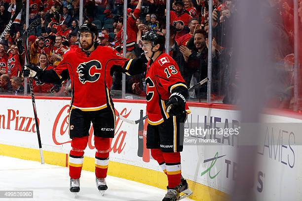 Johnny Gaudreau and David Jones of the Calgary Flames celebrate a goal against the Dallas Stars during an NHL game at Scotiabank Saddledome on...