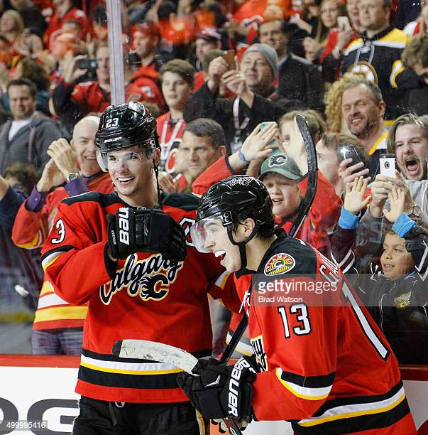 Johnny Gaudreau and Sean Monahan of the Calgary Flames celebrate after an OT goal against the Boston Bruins at Scotiabank Saddledome on December 4...