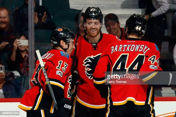 Johnny Gaudreau Dougie Hamilton and teammates of the Calgary Flames celebrate a goal against the Colorado Avalanche during an NHL game on March 27...