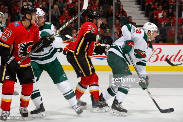 Johnny Gaudreau Micheal Ferland of the Calgary Flames and Cal OReilly of the Minnesota Wild in an NHL game against the Minnesota Wild at the...