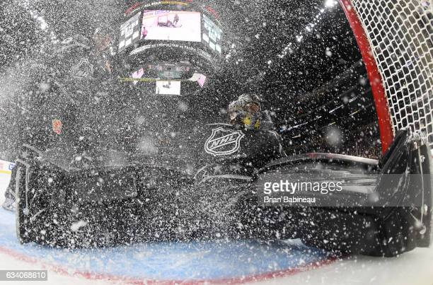 Johnny Gaudreau of the Calgary Flames and Mike Smith of the Arizona Coyotes can't stop the puck going into the net on a second shot on goal by Cam...