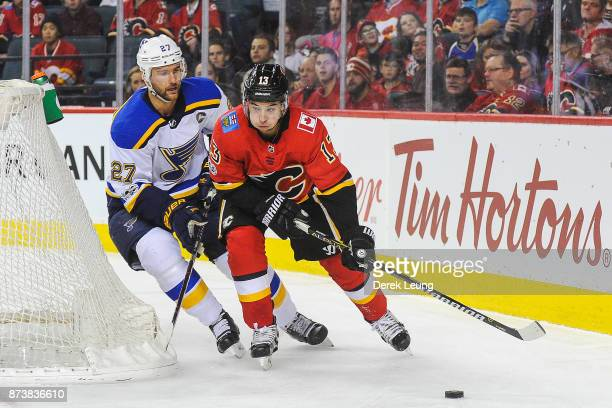 Johnny Gaudreau of the Calgary Flames carries the puck against Alex Pietrangelo of the St Louis Blues during an NHL game at Scotiabank Saddledome on...