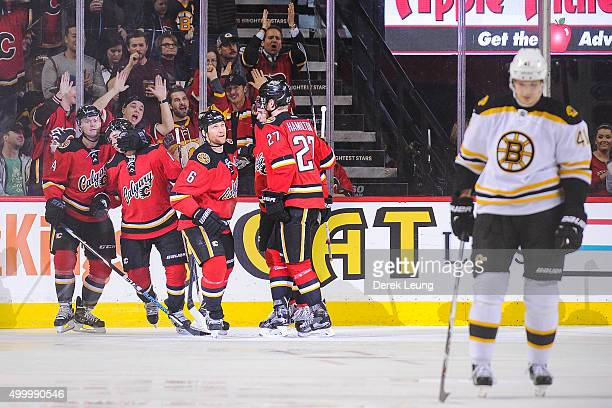 Johnny Gaudreau of the Calgary Flames celebrates with his teammates after scoring against the Boston Bruins during an NHL game at Scotiabank...