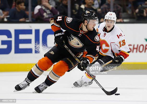 Johnny Gaudreau of the Calgary Flames chases Cam Fowler of the Anaheim Ducks as he skates with the puck during a game at Honda Center on November 24...