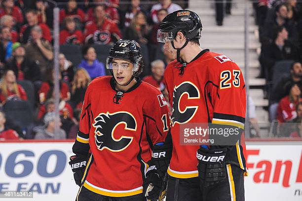 Johnny Gaudreau of the Calgary Flames confers with his teammate Sean Monahan during a break in play against the Detroit Red Wings during an NHL game...