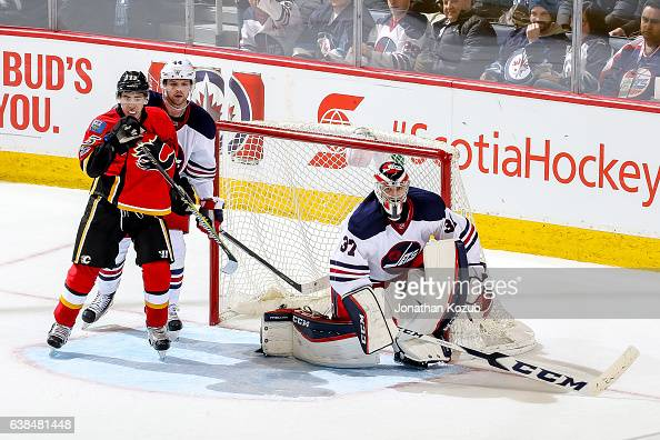 Johnny Gaudreau of the Calgary Flames Josh Morrissey and goaltender Connor Hellebuyck of the Winnipeg Jets keep an eye on the play at the point...