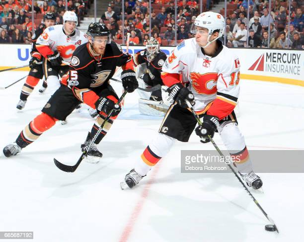 Johnny Gaudreau of the Calgary Flames passes the puck with pressure from Korbinian Holzer of the Anaheim Ducks during the second period of the game...