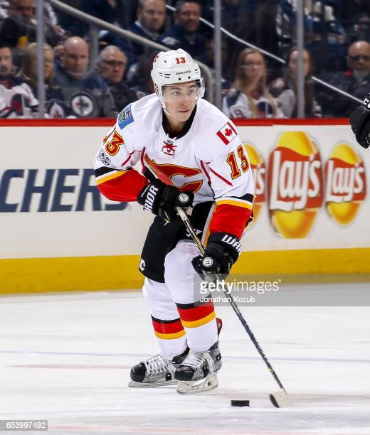 Johnny Gaudreau of the Calgary Flames plays the puck down the ice during third period action against the Winnipeg Jets at the MTS Centre on March 11...