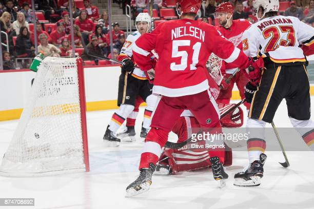 Johnny Gaudreau of the Calgary Flames scores a second period goal on Jimmy Howard of the Detroit Red Wings as Frans Nielsen of the Red Wings and Sean...