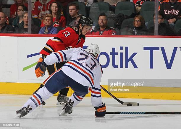 Johnny Gaudreau of the Calgary Flames skates against Matt Hendricks of the Edmonton Oilers at Scotiabank Saddledome on December 27 2014 in Calgary...