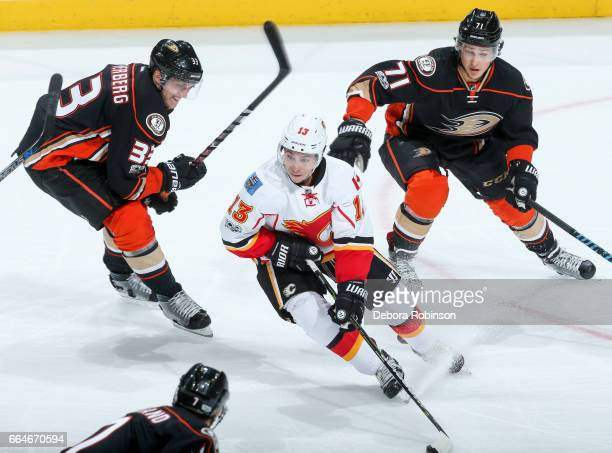Johnny Gaudreau of the Calgary Flames skates with the puck under pressure from Jakob Silfverberg and Brandon Montour of the Anaheim Ducks during the...