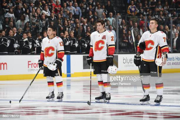 Johnny Gaudreau Sean Monahan and Micheal Ferland of the Calgary Flames stand for the National Anthem before a game against the Los Angeles Kings at...