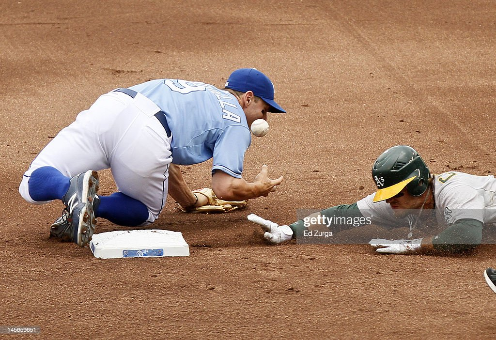 Johnny Giavotella #9 of the Kansas City Royals can't control the ball as Collin Cowgill #12 of the Oakland Athletics slides safely into second in the first inning at Kauffman Stadium June 3, 2012 in Kansas City, Missouri.