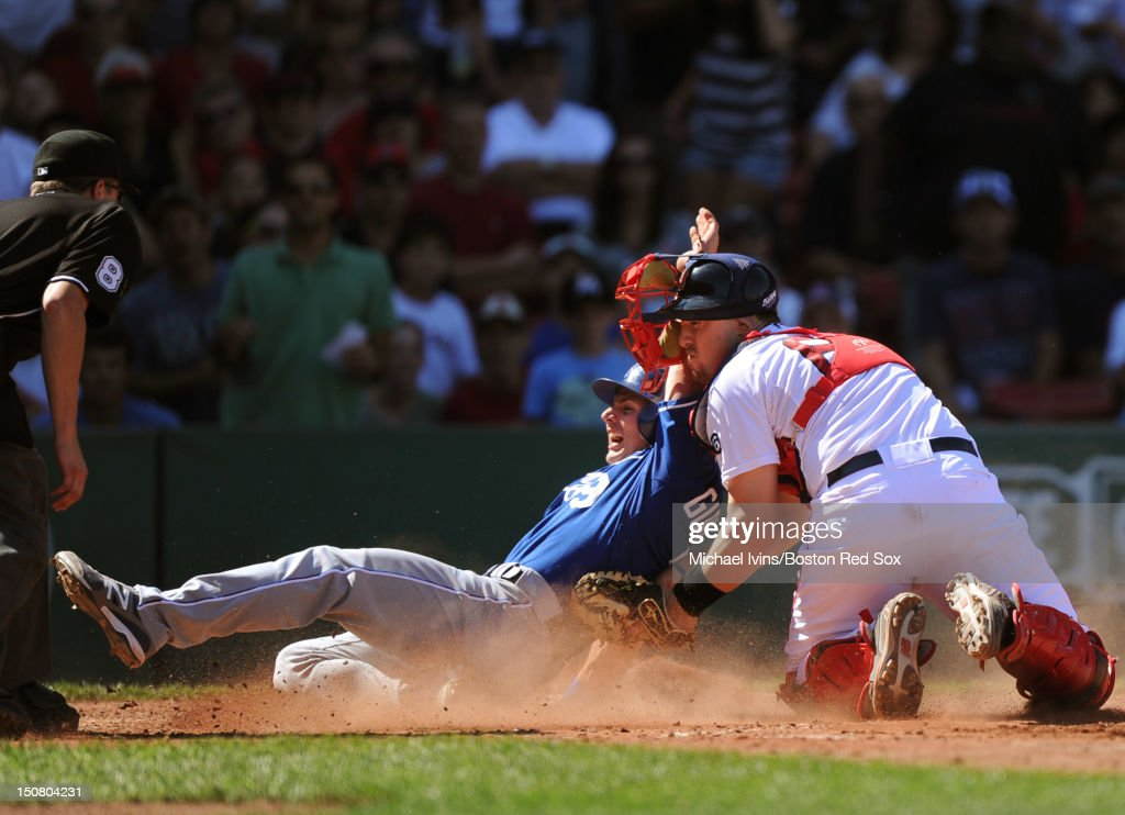 Johnny Giavotella #9 of the Kansas City Royals slides underneath the tag of Ryan Lavarnway #60 of the Boston Red Sox to score a run in the fourth inning on August 26, 2012 at Fenway Park in Boston, Massachusetts.