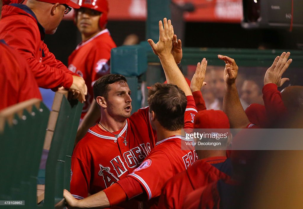 Johnny Giavotella #12 of the Los Angeles Angels of Anaheim celebrates with teammate David Freese #6 in the dugout after scoring on a double to right center by teammate Matt Joyce #20 (not in photo) in the eighth inning during the MLB game against the Colorado Rockies at Angel Stadium of Anaheim on May 12, 2015 in Anaheim, California. The Angels defeated the Rockies 5-2.