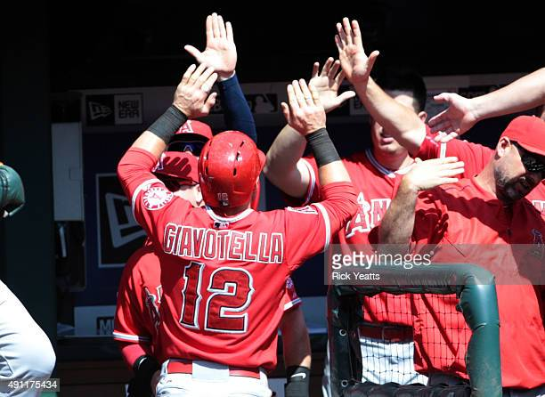 Johnny Giavotella of the Los Angeles Angels of Anaheim is congratulated by teammates for scoring in the fifth inning against the Los Angeles Angels...