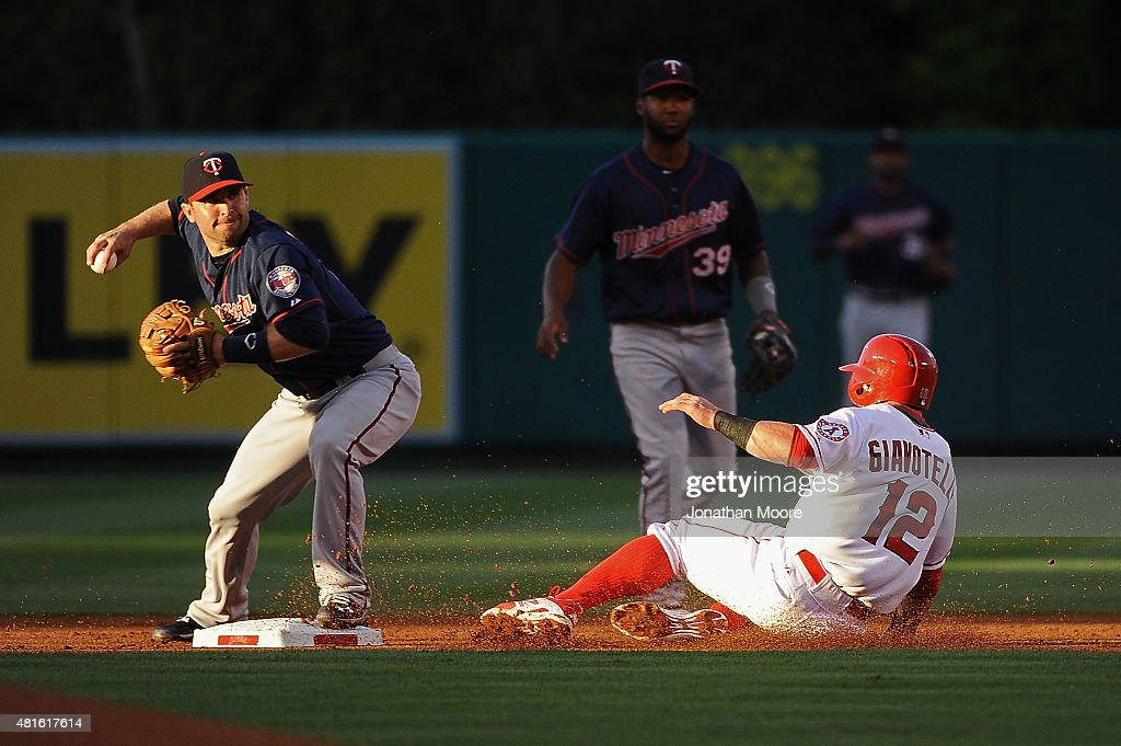 Johnny Giavotella of the Los Angeles Angels of Anaheim is tagged out at second base by Brian Dozier of the Minnesota Twins during the first inning at...