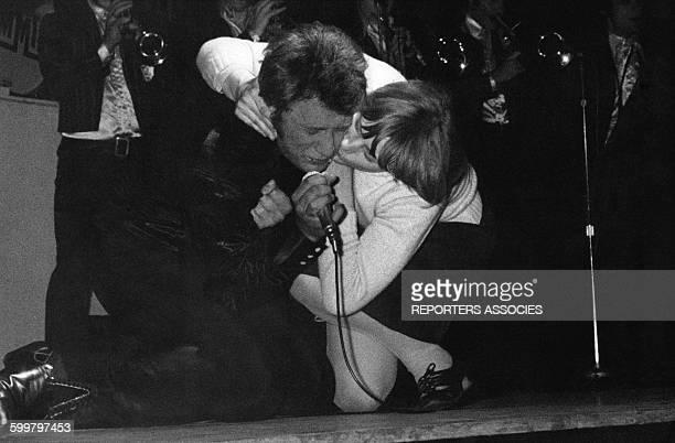 Johnny Hallyday se fait embrasser par une fan sur scène lors d'un concert en France circa 1960