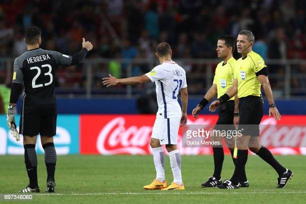 Johnny Herrera of Chile and Marcelo Diaz of Chile argue with referee Damir Skomina and his assistant at half time during the FIFA Confederations Cup...