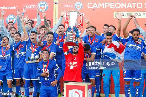 Johnny Herrera of Universidad de Chile lifts the championship cup from the podium after winning a match between Universidad de Chile v San Luis de...