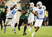 Johnny Jefferson of the Baylor Bears carries while defended by Dominquie Green and Des Lawrence of the North Carolina Tar Heels during the first half...