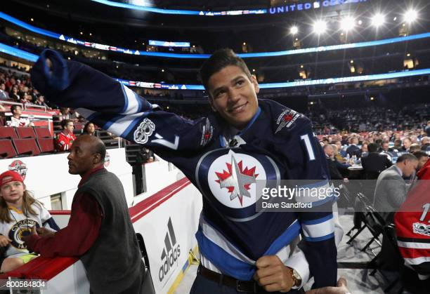 Johnny Kovacevic puts on his jersey after being selected 74th overall by the Winnipeg Jets during the 2017 NHL Draft at United Center on June 24 2017...