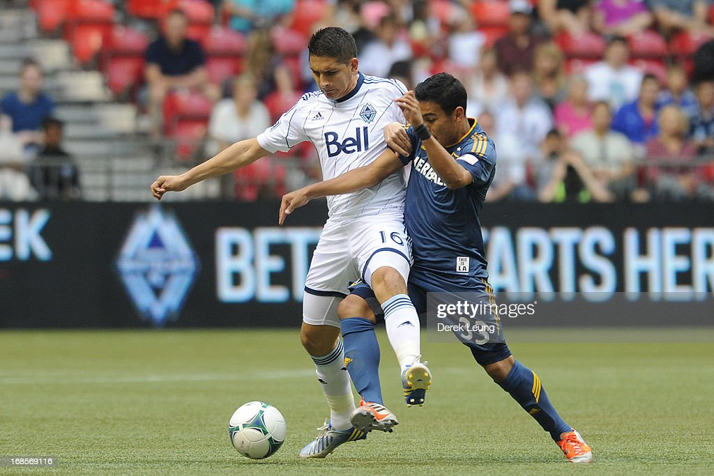 Johnny Leveron #16 of the Vancouver Whitecaps battles for the ball against Jose Villarreal #33 of the Los Angeles Galaxy at B.C. Place on May 11, 2013 in Vancouver, British Columbia, Canada.