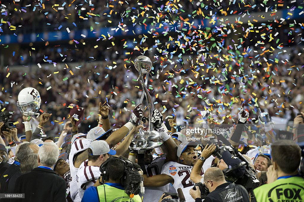 Johnny Manziel #2 and Dustin Harris #22 of the Texas A&M Aggies raise the trophy after defeating the Oklahoma Sooners in the AT&T Cotton Bowl on January 4, 2013 at Cowboys Stadium in Arlington, Texas.