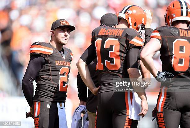 Johnny Manziel looks on while Josh McCown of the Cleveland Browns huddles with teammates during the second quarter against the Oakland Raiders at...