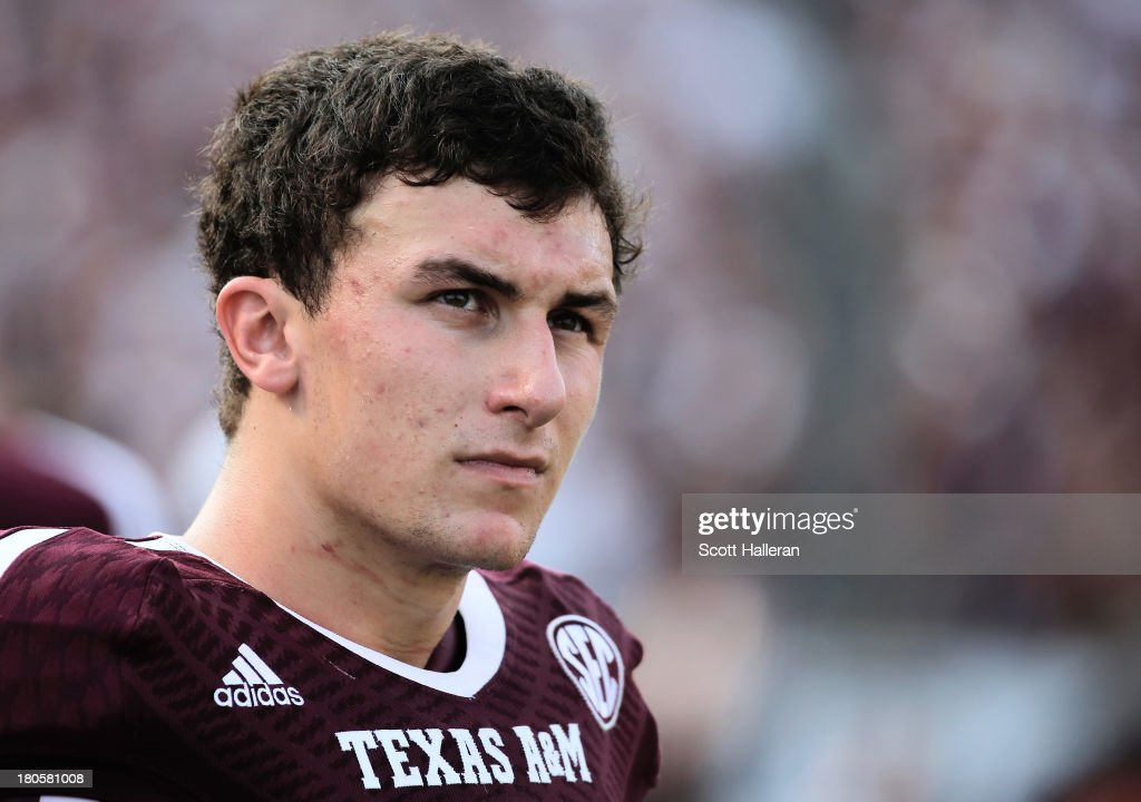Johnny Manziel of Texas AM Aggies waits near the bench in the fourth quarter during the game against the Alabama Crimson Tide at Kyle Field on...