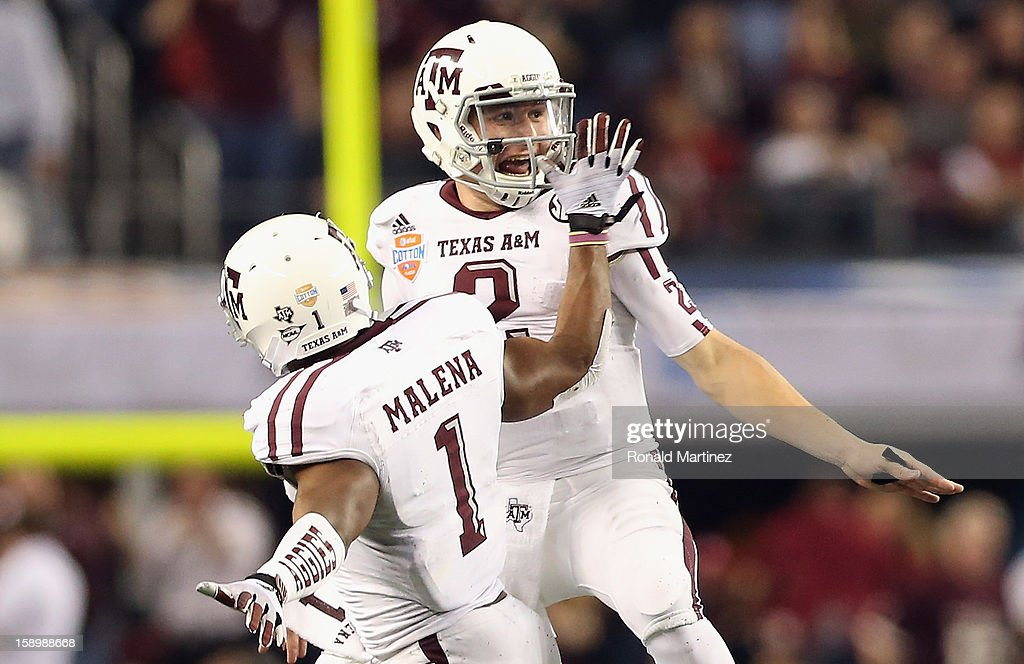 Johnny Manziel #2 of the Texas A&M Aggies celebrates a touchdown with Ben Malena #1 against the Oklahoma Sooners during the Cotton Bowl at Cowboys Stadium on January 4, 2013 in Arlington, Texas.