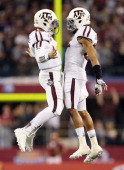 Johnny Manziel of the Texas AM Aggies celebrates a touchdown with Dustin Harris against the Oklahoma Sooners during the Cotton Bowl at Cowboys...