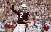 Johnny Manziel of the Texas AM Aggies celebrates after throwing a first quarter touchdown during a game against the Alabama Crimson Tide at Kyle...