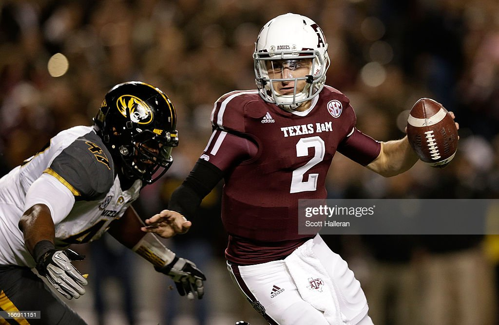 Johnny Manziel #2 of the Texas A&M Aggies runs away from the tackle of Kony Ealy #47 of the Missouri Tigers at Kyle Field on November 24, 2012 in College Station, Texas.