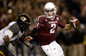 Johnny Manziel of the Texas AM Aggies runs away from the tackle of Kony Ealy of the Missouri Tigers at Kyle Field on November 24 2012 in College...
