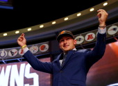 Johnny Manziel of the Texas AM Aggies takes the stage after he was picked overall by the Cleveland Browns during the first round of the 2014 NFL...
