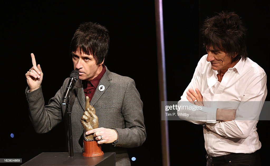 Johnny Marr is presented the Godlike Genius award by Ronnie Wood at the NME Awards 2013 at the Troxy on February 27, 2013 in London, England.