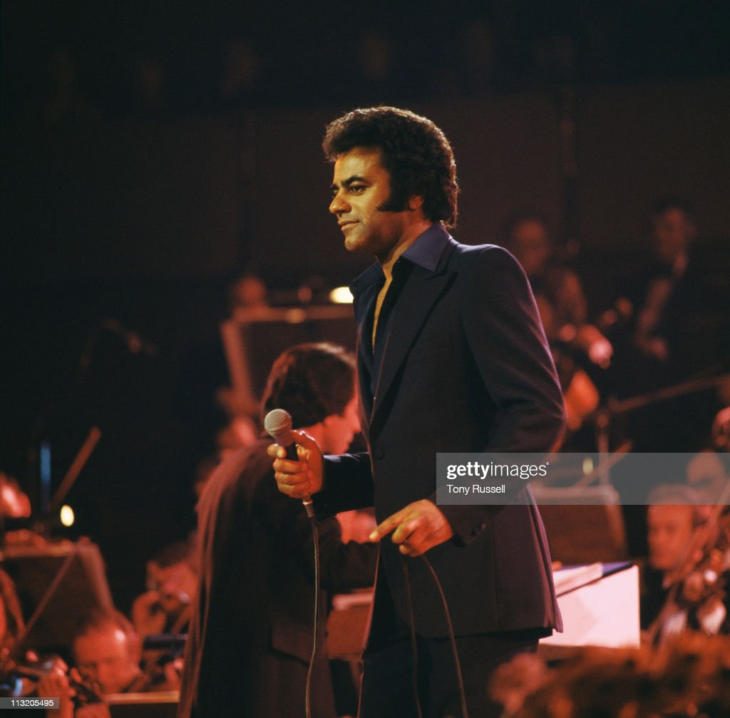 Johnny Mathis US singer holding a microphone during a live concert performance in London England Great Britain circa 1977 An orchestra is visible in...