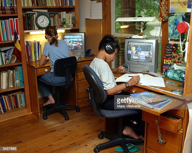 Johnny McLean and his adopted sister Katie work on home schooling video lessons at the family's farmhouse April 22 2004 in Shreveport Louisiana The...