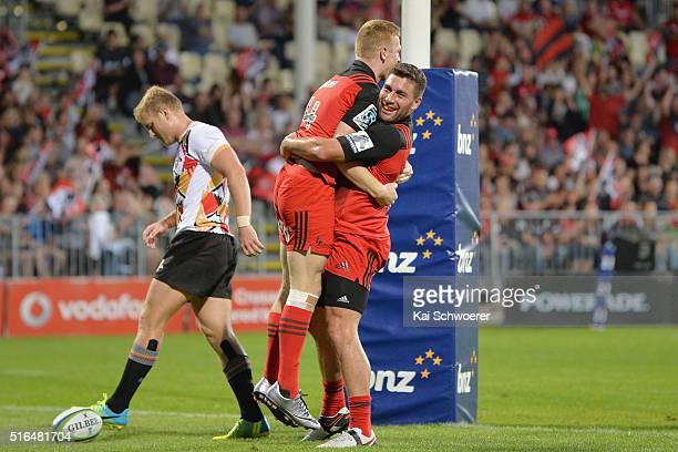Johnny McNicholl of the Crusaders celebrates scoring a try with Kieron Fonotia while Shane Gates of the Kings reacts during the round four Super...