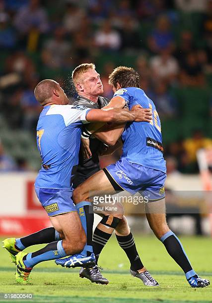 Johnny McNicholl of the Crusaders gets tackled by Matt Hodgson and Peter Grant of the Force during the round seven Super Rugby match between the...