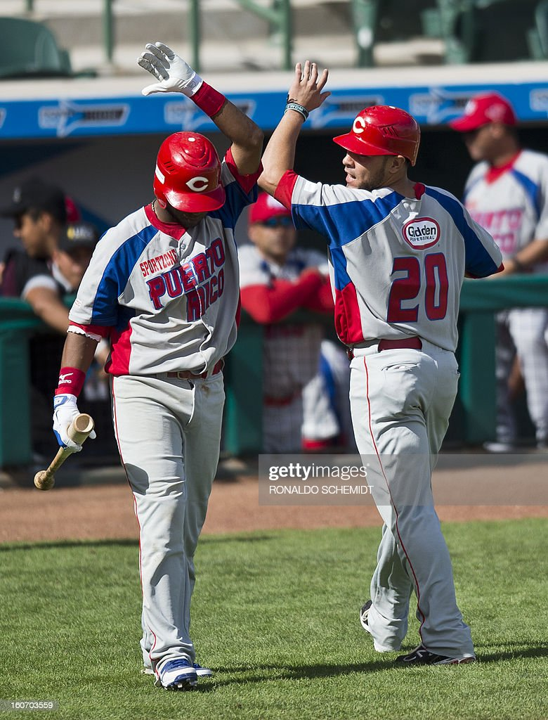 Johnny Monell (R) of Criollos de Caguas of Puerto Rico, celebrates in a match against Leones del Escogido of Dominican Republic, during the 2013 Caribbean baseball series, on February 4, 2013, in Hermosillo, Sonora State, in the northern of Mexico. AFP PHOTO/Ronaldo Schemidt